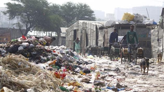 On a typical day in the slums of Nathupur, a village that borders Cyber City and DLF Phase 3, men can be seen sifting through the garbage that arrives in trucks.(Yogendra Kumar/HT PHOTO)