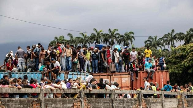 Venezuelans remain on top of containers as they attempt to cross the blocked Simon Bolivar international bridge, in Cucuta, Colombia, in the border with Venezuela.(AFP)