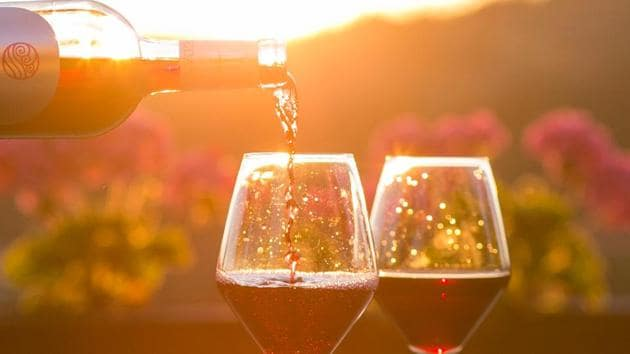 Wine being poured into two glasses at a picturesque location.(Unsplash)