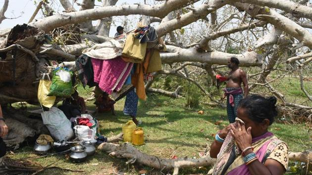 A tribal family seen under a collapsed tree that was hit by cyclone Fani, at Birapratap Pur Village, Odisha, India, on Thursday, May 09, 2019.(Photo: Arabinda Mahapatra / Hindustan Times)