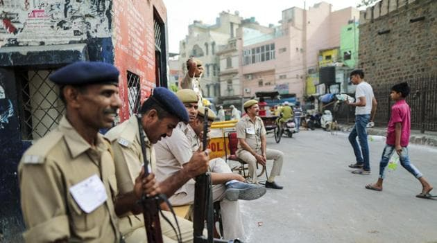Security officers sit outside a polling station during the sixth phase of voting for national elections(Bloomberg)