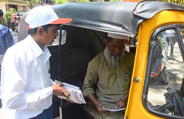 Nitin Kadam, a volunteer distributes books to an autorickshaw driver in Pune(Shankar Narayan/HT PHOTO)