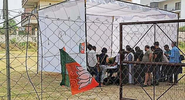 Similarly, in Sector 69, two polling assistance booths right outside the polling booth in Tulip White had flags of two political parties affixed to metal poles supporting the tent around 9.30am.(HT Photo)