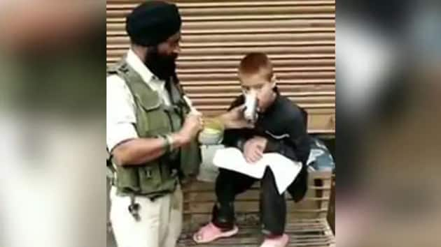 A grab from the video showing CRPF Head Constable Iqbal Singh feeding a differently-abled child in Srinagar's old city area.(HT PHOTO)