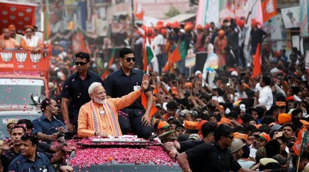 Prime Minister Narendra Modi waves towards his supporters during a roadshow in Varanasi, on April 25, 2019. Varanasi is the most high-profile constituency going to the polls in the last phase on May 19.(REUTERS)