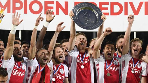 Ajax Amsterdam's captain Matthijs de Ligt holds the champions plate as he celebrates with team mates.(AFP)
