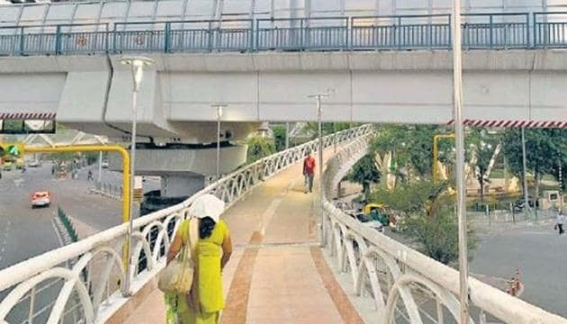 Most people use the Pragati Maidan skywalk or footbridges for the purpose they were inaugurated last year for —to walk to their respective destinations without having to cross the traffic-clogged roads.(HT Photo)