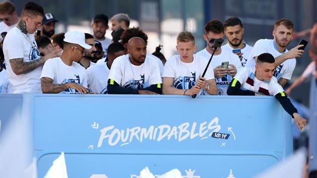 Manchester City players, including Manchester City's Brazilian goalkeeper Ederson (L) and Manchester City's English midfielder Fabian Delph (C), Manchester City's Ukrainian midfielder Oleksandr Zinchenko (center R) and Manchester City's English midfielder Phil Foden (R) take part in an open-top bus parade through Manchester(AFP)