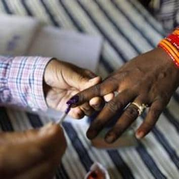 Lok Sabha election 2019: A polling officer puts indelible ink mark on the index finger of an women voter at a polling station, on the outskirts of Varanasi.(AP)