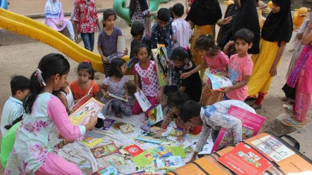 Thane, India - May.25,2019:Children in Mumbra gather excitedly at parks and gardens to read from the suitcase library initiative ,India, on Saturday, May 25, 2019. ( Praful Gangurde/ HT Photo)