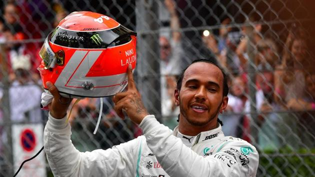 Mercedes' British driver Lewis Hamilton points at the name of late Formula One legend Niki Lauda on his helmet after winning the Monaco Formula 1 Grand Prix at the Monaco street circuit on May 26, 2019 in Monaco(AFP)