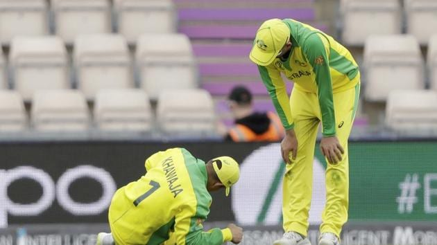 Australia's Usman Khawaja, left, lies down with an injury he picked up fielding before he was helped to limp off the field of play during the Cricket World Cup warm-up match between Australia and Sri Lanka at the Hampshire Bowl in Southampton, England, Monday, May 27, 2019. (AP Photo/Matt Dunham)(AP)
