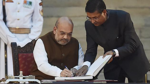 Bharatiya Janata Party (BJP) national president Amit Shah signs the documents after taking oath during a swearing-in ceremony, at the forecourt of Rashtrapati Bhavan in New Delhi, on Thursday, May 30, 2019.(Ajay Aggarwal/HT PHOTO)