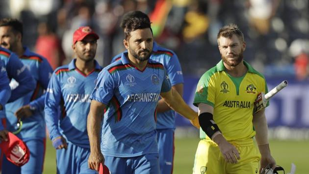 Australia's David Warner, right, and Afghanistan's captain Gulbadin Naib leave the field after the Cricket World Cup match between Afghanistan and Australia at Bristol County Ground in Bristol, England, Saturday, June 1, 2019. Australia won by seven wickets.(AP)