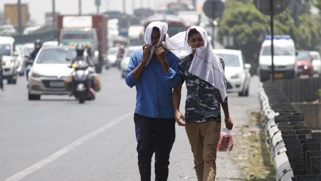 People cover themselves to beat the heat on a summer day, in Gurugram.(Yogendra Kumar/HT PHOTO)