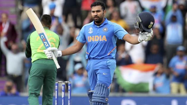 India's Rohit Sharma raises his bat and helmet to celebrate scoring a century.(AP)