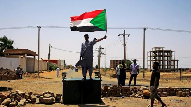 A Sudanese protester holds a national flag as he stands on a barricade along a street, demanding that the country's Transitional Military Council hand over power to civilians, in Khartoum, Sudan.(Reuters Photo)