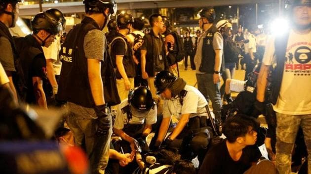 Police officers detain protesters during a protest to demand authorities scrap a proposed extradition bill with China, on Gloucester Road in Hong Kong, China June 10, 2019.(REUTERS)