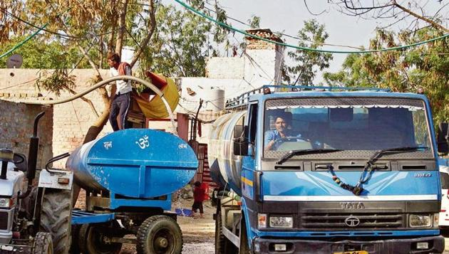 A man fills a water tanker, in Gurugram. The city's water mafia is controlled by people who operate from remote villages in the district. These are the ones who supply water tankers to meet rising demand during the peak summer season, and who are also involved in breaking water pipelines to ensure that their business flourishes.(Yogendra Kumar/Hindustan Times)