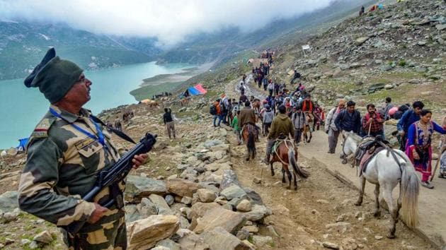 Security personnel look on as a batch of pilgrims are on their way towards the holy cave shrine of Amarnath. (PTI file Photo)