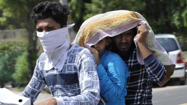 Noida, India - June 10, 2019: Boys on a two-wheeler cover themselves with a cloth to beat the heat on a summer day, in Noida, India, on Monday, June 10, 2019. (Photo by / Hindustan Times)(Sunil Ghosh /HT Photo/Representative Image)