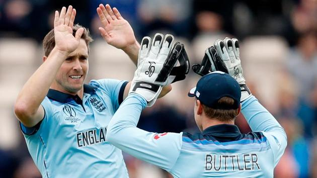 England's Chris Woakes (L) celebrates with England's wicketkeeper Jos Buttler after the dismissal of West Indies' Evin Lewis.(AFP)