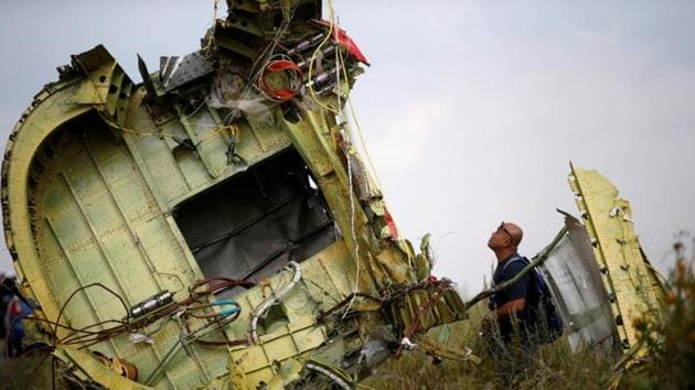 An investigator inspects the crash site of flight MH17, near the village of Hrabove in Donetsk, Ukraine on July 22, 2014. REUTERS/Maxim Zmeyev/File Photo