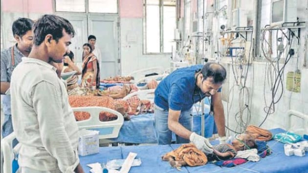 A doctor treats a child with Acute Encephalitis Syndrome (AES)-like symptoms at Patna Medical College and Hospital on June 17.