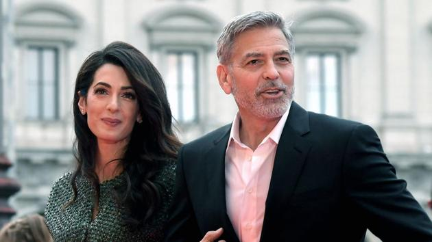 US actor George Clooney (R) and wife British-Lebanese Amal Clooney arrive to the premiere of Catch-22.(AFP)