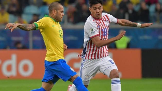 Brazil's Dani Alves (L) and Paraguay's Santiago Arzamendia vie for the ball.(AFP)