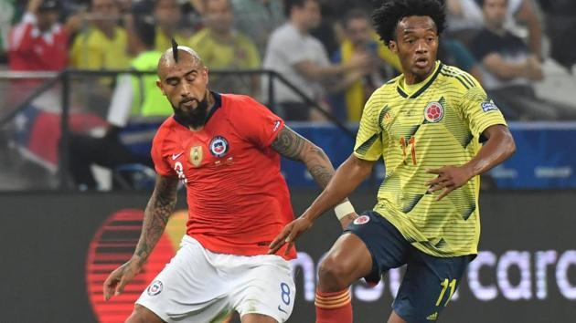 Colombia's Juan Guillermo Cuadrado (R) is marked by Chile's Arturo Vidal during their Copa America football tournament.(AFP)