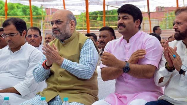 Union Home Minister Amit Shah along with Delhi BJP President Manoj Tiwari, MPs Hans Raj Hans and Parvesh Verma listen to Prime Minister Narendra Modi's radio show 'Man Ki Baat' at Dr Sahib Singh Verma Stadium Kakrola in New Delhi on Sunday. (ANI Photo)