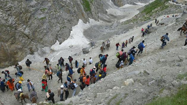 Pilgrims trek to the holy cave shrine of Amarnath, in Baltal, Jammu and Kashmir on Monday.(PTI)