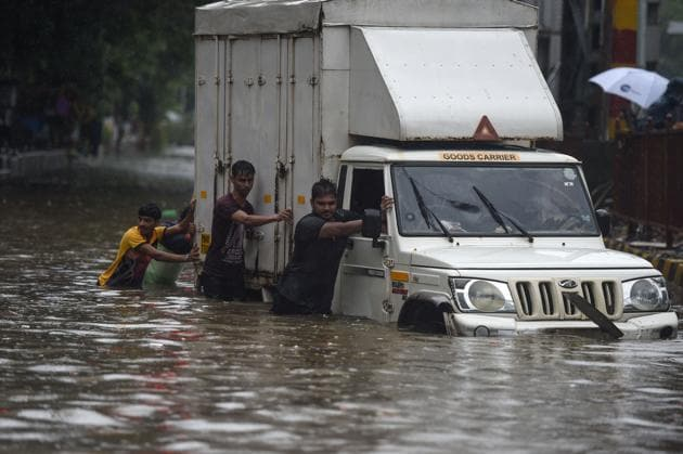 Indian men push a truck along a flooded street after heavy rain showers in Mumbai on July 1, 2019.(AFP)