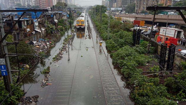 Train services on Mumbai's colonial-era rail network, a lifeline for the city's population, were reduced due to waterlogged tracks while motorists were seen pushing cars through flooded streets.(Photo: Kunal Patil/ Hindustan Times)