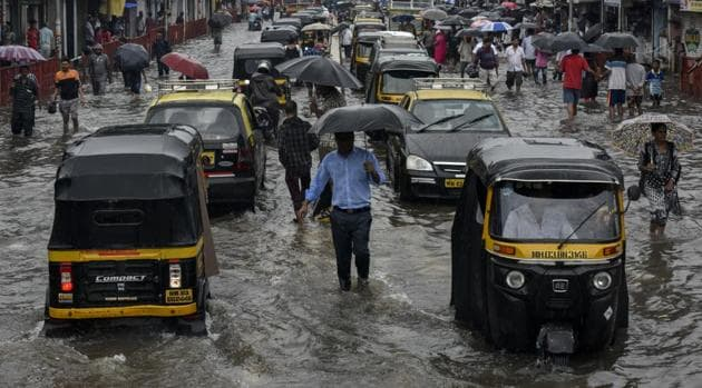 People walk along a flooded street after heavy rain showers outside Kurla station in Mumbai, India, on Tuesday, July 2, 2019.(Kunal Patil/HT Photo)