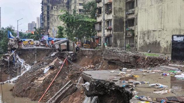 A road caves in following heavy monsoon rains, at Sangharsh Nagar in Mumbai.(PTI)