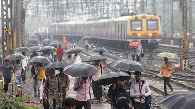 Commuters walk on track near thane railway station after train stop for mumbai Thane. ( Praful Gangurde/ HT Photo)