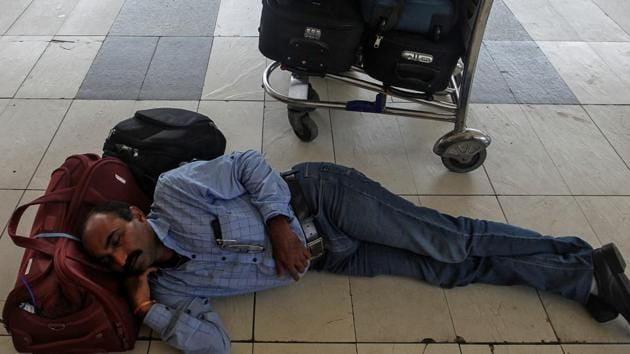 A stranded passenger sleeps next to his luggage as he waits for the delayed flight after an airplane overshot the runway while landing due to heavy rains at the Chhatrapati Shivaji International airport in Mumbai, India July 2, 2019. REUTERS/Prashant Waydande(REUTERS)