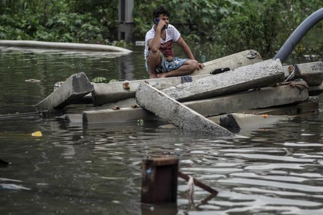 A man talks on a mobile phone while sitting on blocks of concrete surrounded by flood waters in the Tilak Nagar area of Mumbai, India, on Tuesday, July 2, 2019. The heaviest downpour since 2005 inundated Mumbai, delaying trains and planes and spurring the city administration to declare a holiday.(Bloomberg)