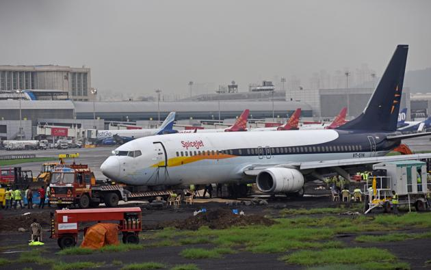 A team from Air India is heading the operations to tow away the SpiceJet aircraft which overshot the runway on Monday.(Satyabrata Tripathy/HT Photo)