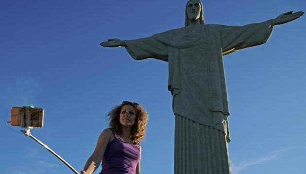 A tourist takes a selfie by the Christ the Redeemer statue(AFP)