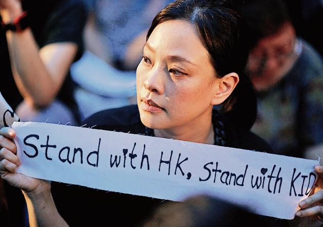 A woman holds a placard during a gathering of Hong Kong mothers to show their support for the city's young pro-democracy protesters in Hong Kong, China, July 5, 2019(REUTERS)