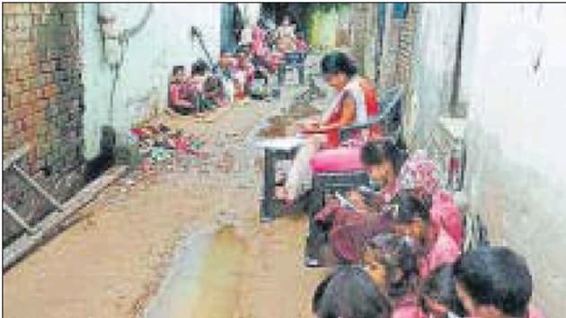 Students in basic education department schools here are forced to study in the open, even during the rainy season, due to lack of classrooms in rented buildings or because there is no building at all.(HT Photo)