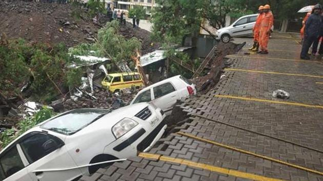 According to residents, labourers should be insured by contractors for safety. (In pic) A displaced car at the site where a compound wall of a society collapsed on shanties adjacent to it in Kondhwa.(HT/PHOTO)