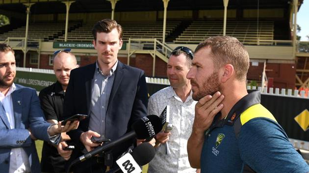 Australia's one-day cricket captain Aaron Finch (R) speaks to the media.(AFP)