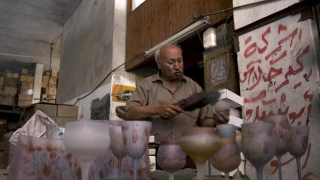 """""""We have been economically damaged. We are staying, but things are really difficult,"""" said Abed Abu Sido, one of Gaza's last glassmakers, as he flipped through a glossy catalog of his products. At his quiet workshop, layers of dust covered the few remaining glass artifacts, requiring him to scrub them to reveal their colors. Cardboard boxes of unfinished products and materials were stacked floor-to-ceiling. (Khalil Hamra / AP)"""