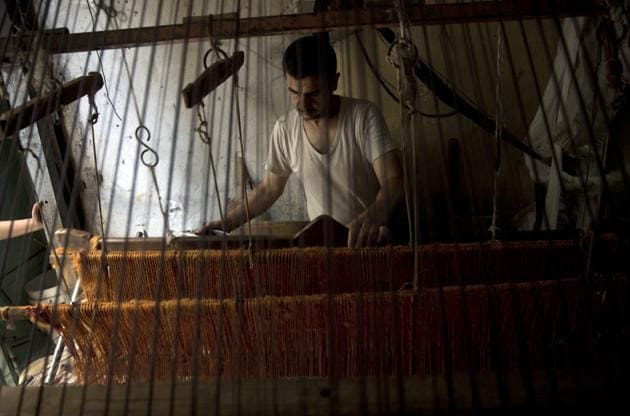 Palestinian worker weaves carpets on a traditional wooden loom at a carpets factory in Gaza City. When Gazans think of better economic times, images of clay pottery, colourful glassware, bamboo furniture and ancient frame looms weaving bright rugs and mats all come to mind. While such professions have shrunk worldwide in the face of globalization and Chinese mass production, Gazan business owners say Israel's 12-year blockade of the territory has accelerated the trend. (Khalil Hamra / AP)