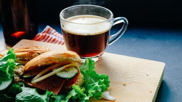 Representational image of a burger with vegetables and a cup of black coffee.(Unsplash)