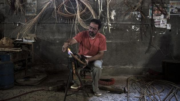 Palestinian Tarek Khalaf uses a flame to form bamboo at his family's workshop. For decades, these traditional crafts defined the economy of the coastal Palestinian enclave, employing thousands of people and exporting across the region. Today, the industries are almost non-existent.Under the blockade, Israel has greatly restricted exports and limited imports of raw materials. With unemployment over 50%, demand from the local market is weak. Israel blames the situation on Hamas, an armed group that opposes Israel's existence. (Khalil Hamra / AP)